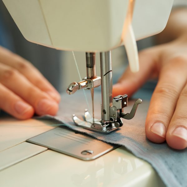 Hands of female tailor using sewing machine at work